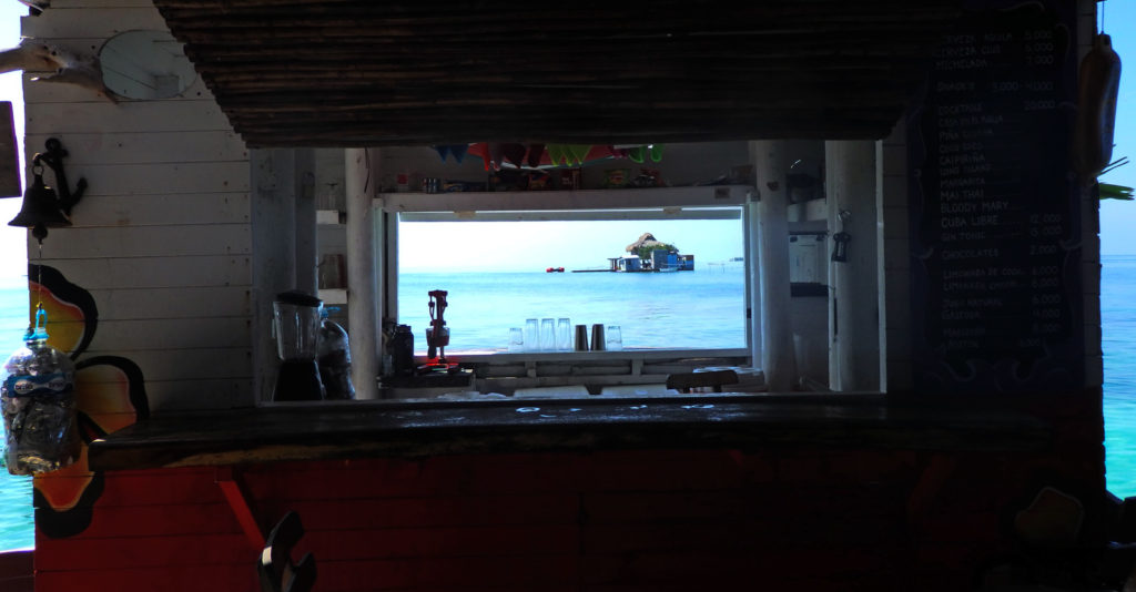 Staying at Casa en el Agua, the hostel in the sea. A view through the bar window looking out over the crystal blue waters