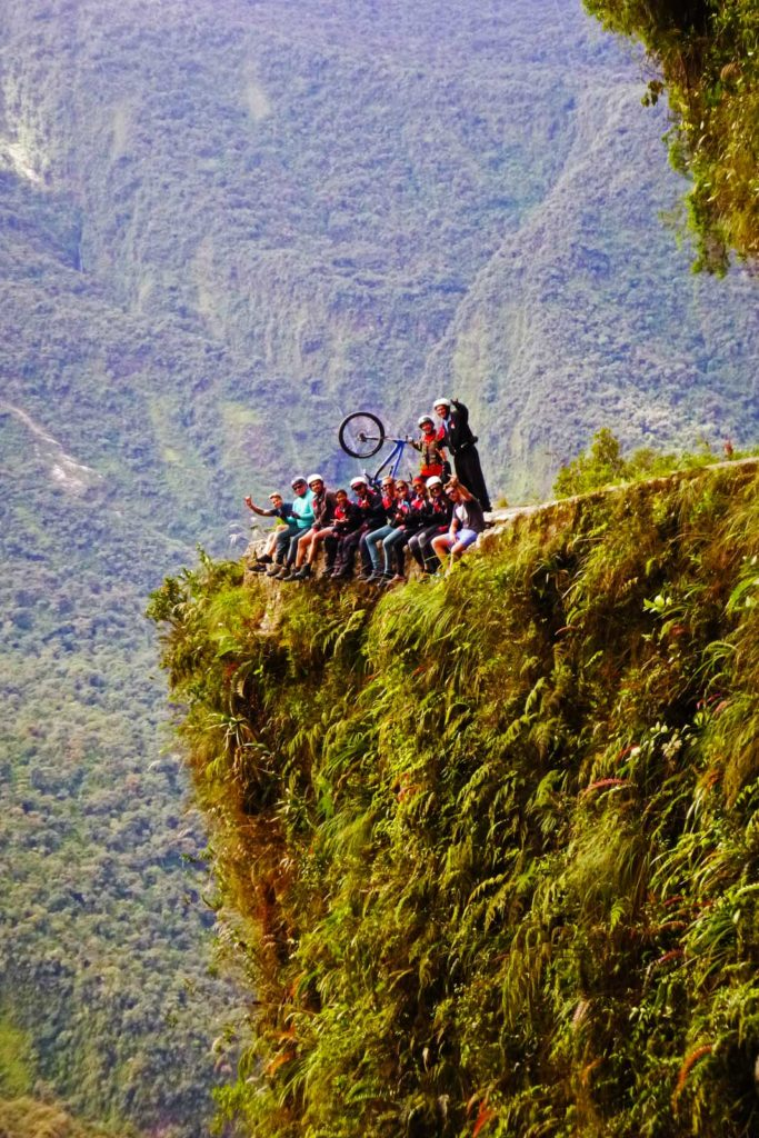 Advice on what to prepare for backpacking La Paz. A group of people sitting on the edge of death road with their legs hanging over the road edge