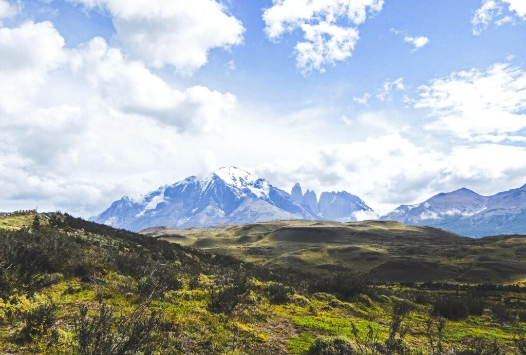 Step by step guide for planning, trekking and travelling Torres Del Paine. Looking out over green hills with Torres Del Paine in the background