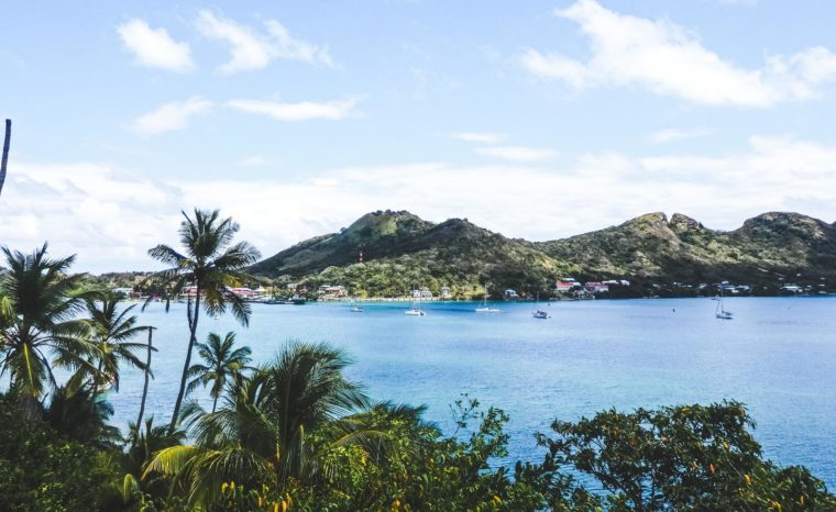 Why travelling Providencia Island shows you true paradise. The view from the adjoining island with palm trees and lush green coast line