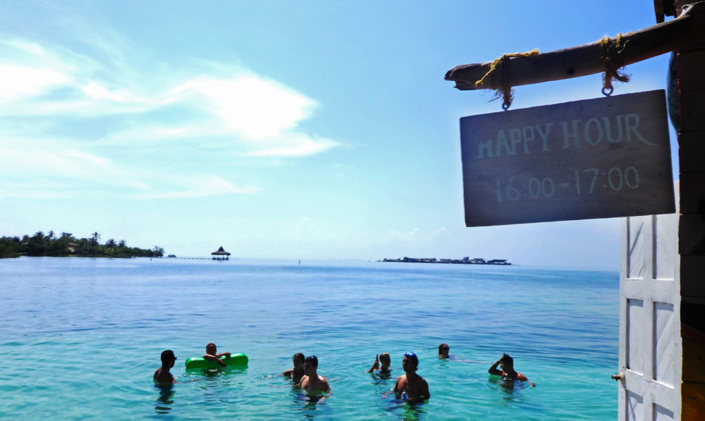 """Staying at Casa en el Agua, the hostel in the sea. A sign says """"happy hour"""" while people stand talking in the shallow sea water"""