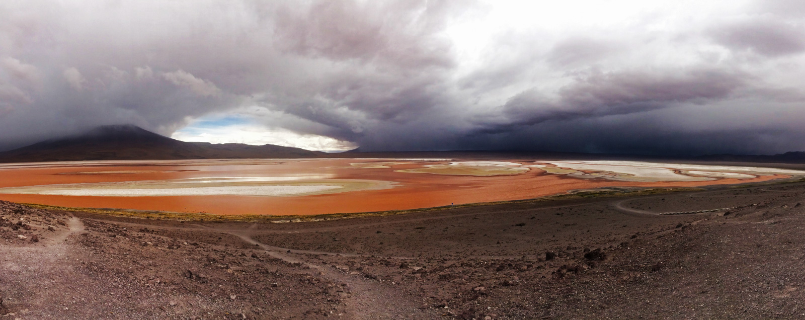 Backpacking the Salt Flats? Here's some useful tips. One of the pink lagoons with low clouds over it surrounded by the rustic coloured earth