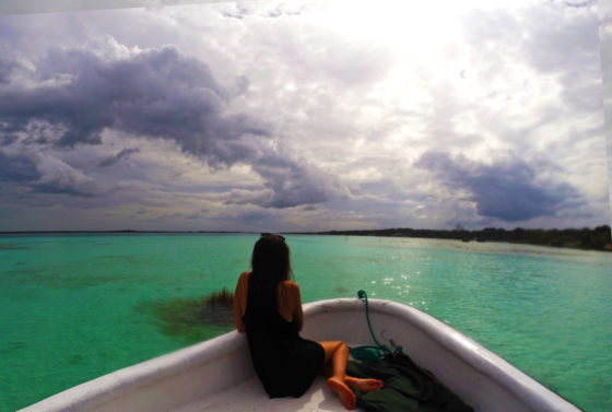 Why travelling Bacalar is spectacular. A girl sits on a boat looking out over the seven colour lake