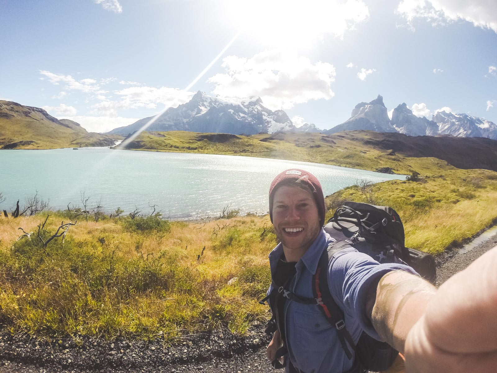 Why you should trek Torres Del Paine before you die. A man smiling into camera whilst walking along the road with Torres Del Paine in the background.