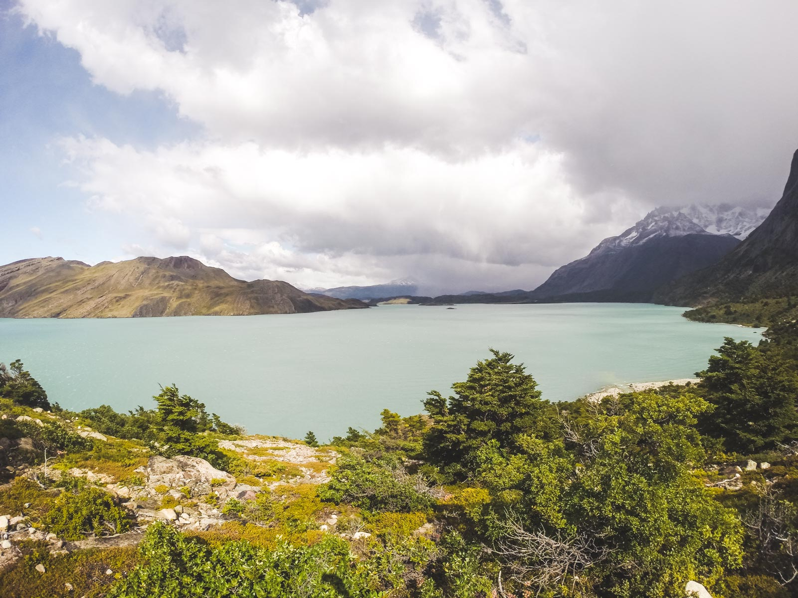 Why you should trek Torres Del Paine before you die. Looking out over the lagoon at the very bottom of the W trek with The Andes mountain range in the background