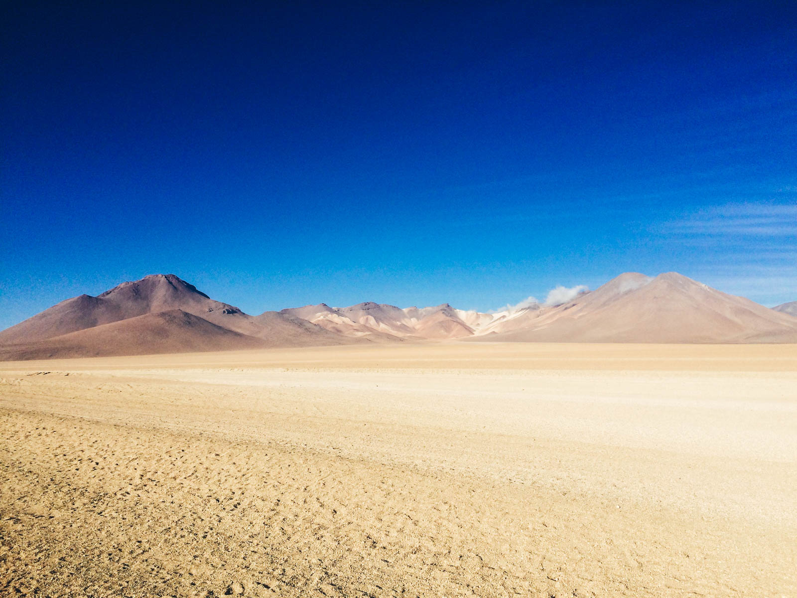 What to expect backpacking Uyuni with advice and tips. The endless desert expanse with mountains in the background