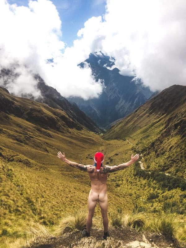 Trekking the Inca Trail to Machu Pichu. Naked boy with his back turned, arms spread looking onto the Andes mountains on the 1st day in the trek