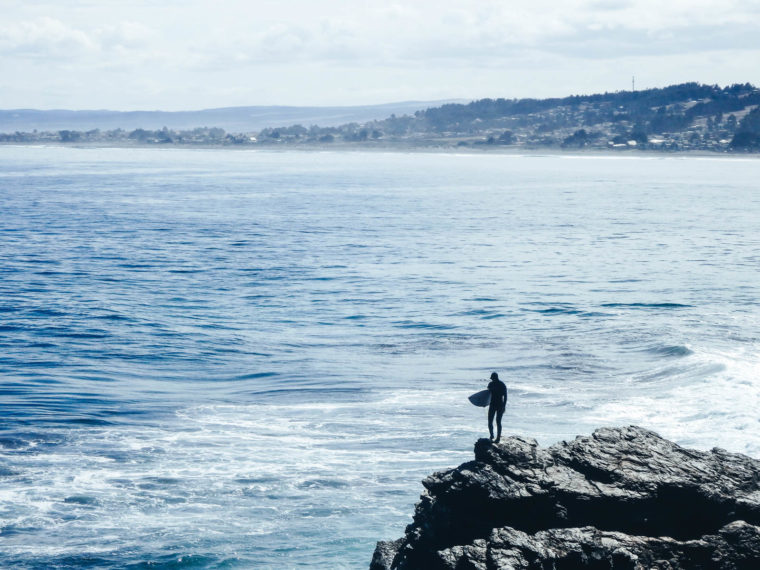 Pichilemu in Chile is a hidden gem to travel. A surfer stands on the rock edge about to jump in