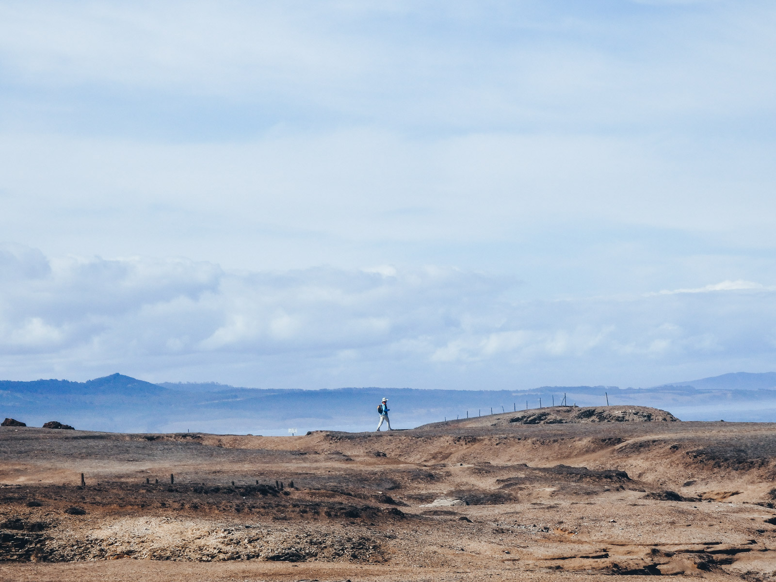 Pichilemu in Chile is a hidden gem to travel. A man walks along the coastline to the beach front in Pichilemu
