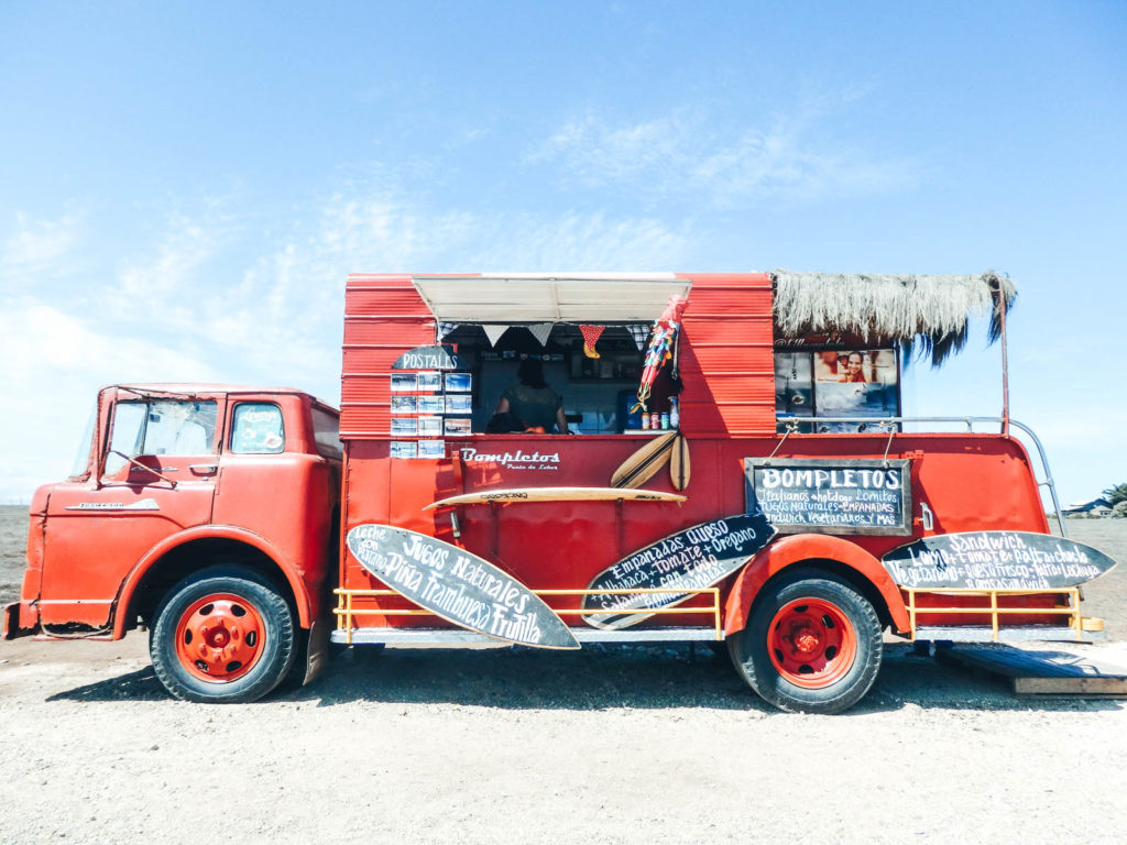 Pichilemu in Chile is a hidden gem to travel. A large red truck on the coastline selling Completos. A must eat in Chile.