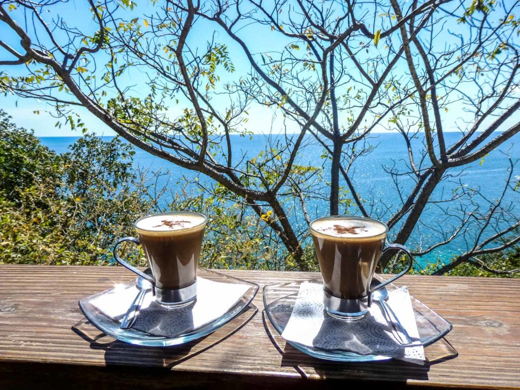 Why travelling Providencia Island shows you true paradise. Two coffees sat on a ledge with a view of the sea and the island i the background