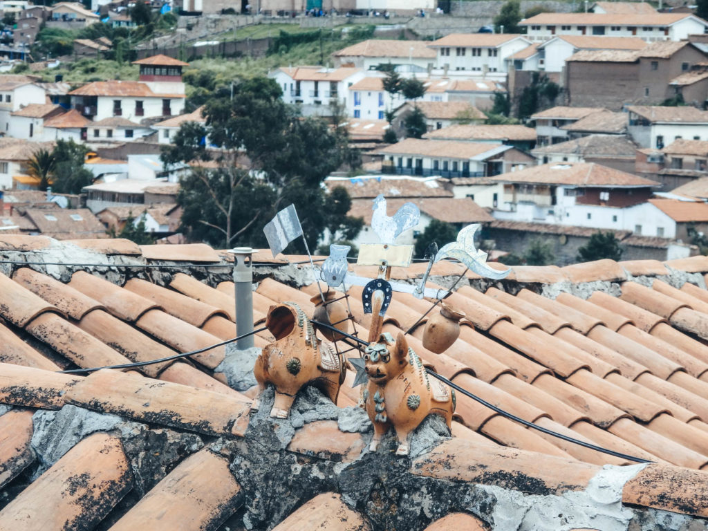 Why travelling Cusco is epic! Two cow ornaments on top of a house in Cusco signifying prosperity