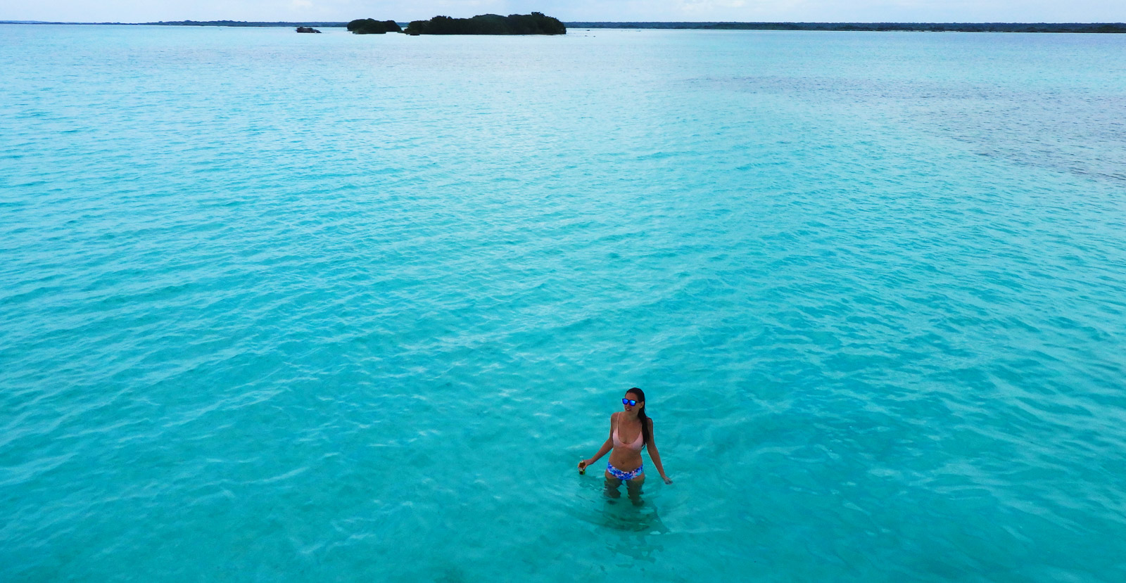 Why travelling Bacalar is spectacular. A girl stands in the blue waters of Bacalars seven colour lake