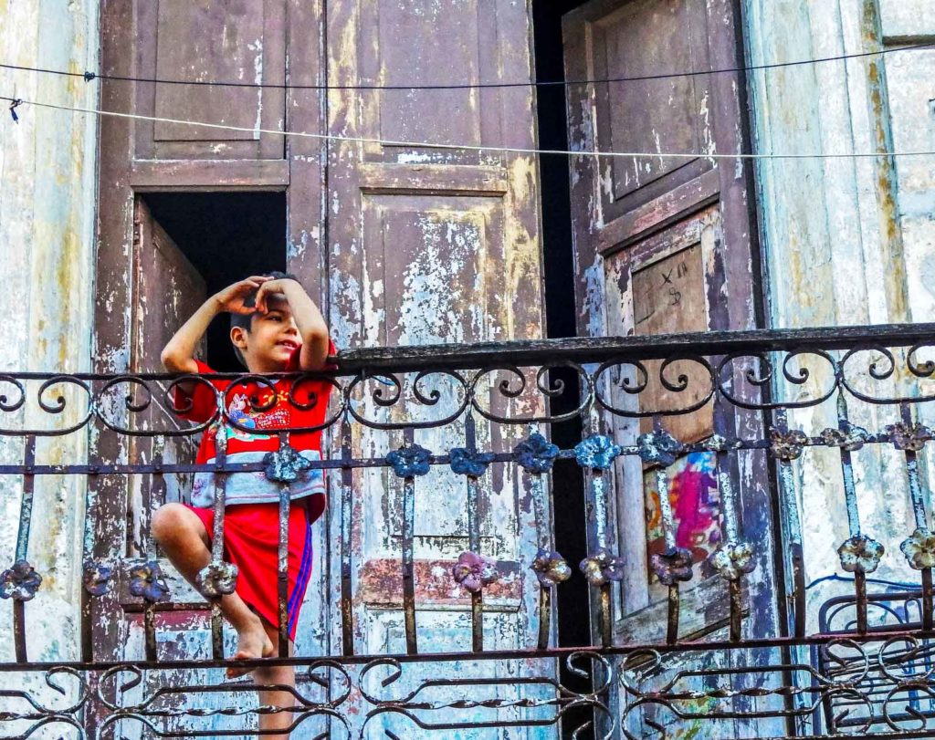Here's why you'll feel at home backpacking Havana. A child stands on a balcony of a Cuban house