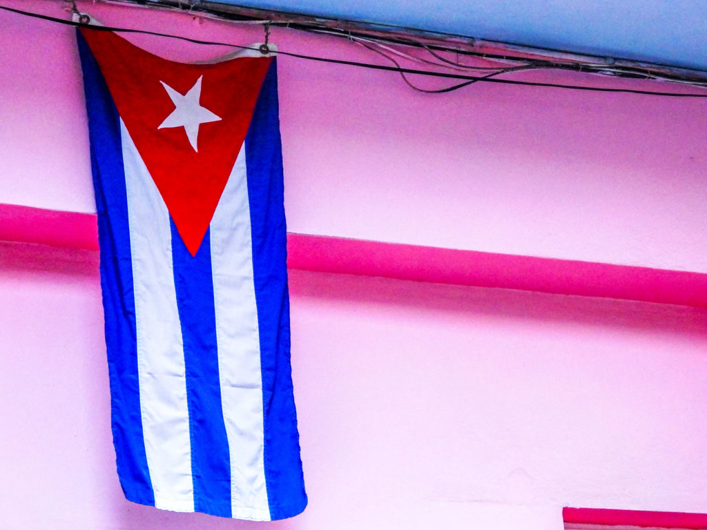 Here's why you'll feel at home backpacking Havana. A Cuban flag hangs in front of a pink building