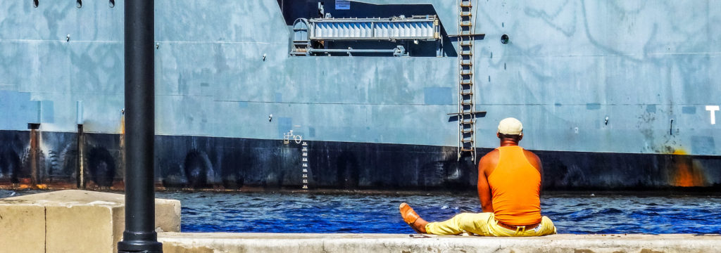 Here's why you'll feel at home backpacking Havana. A man sits on the pier looking out at a navy boat on the Malacon