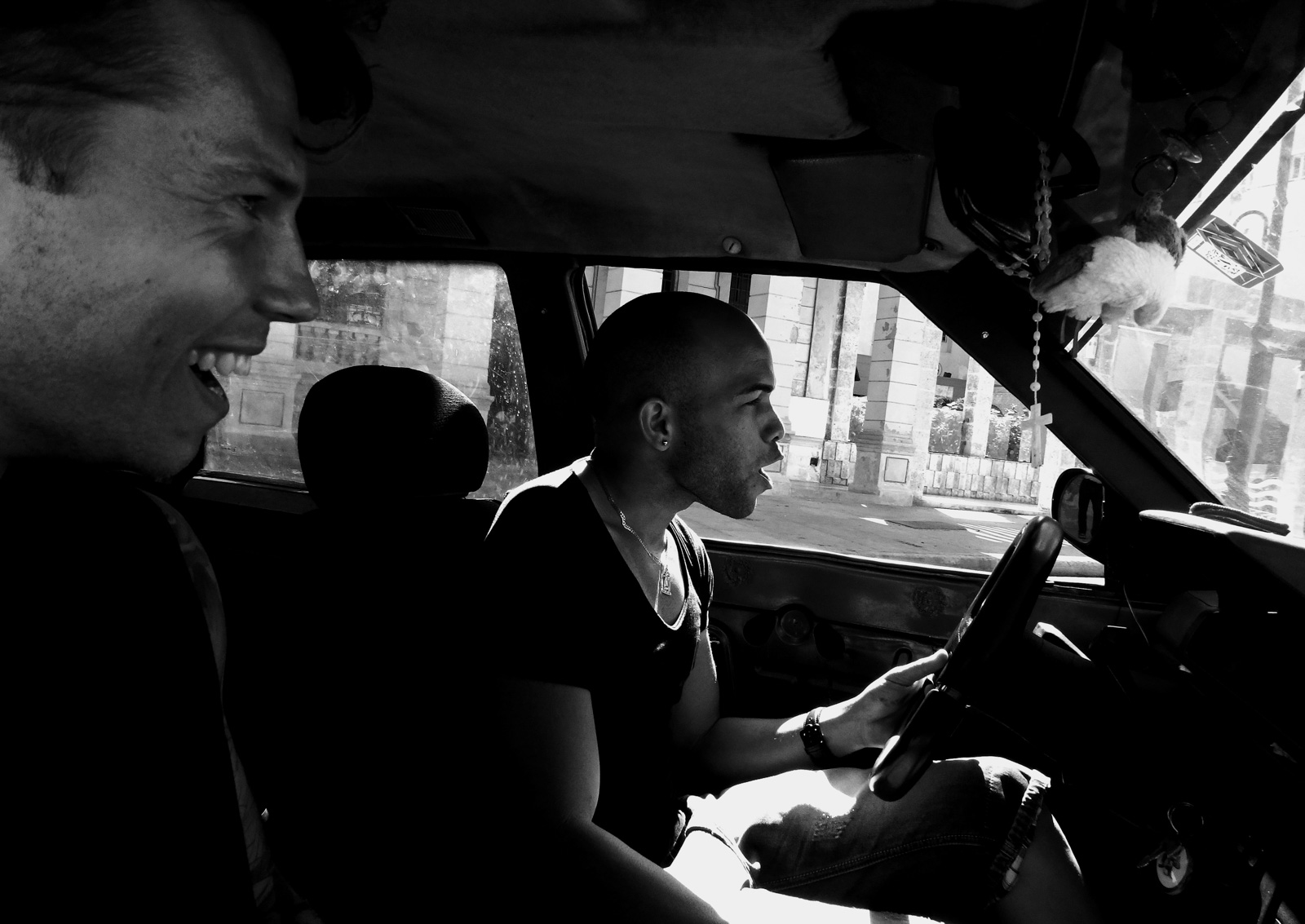Here's why you'll feel at home backpacking Havana. Two people sitting in a car signing while driving along the Malacon