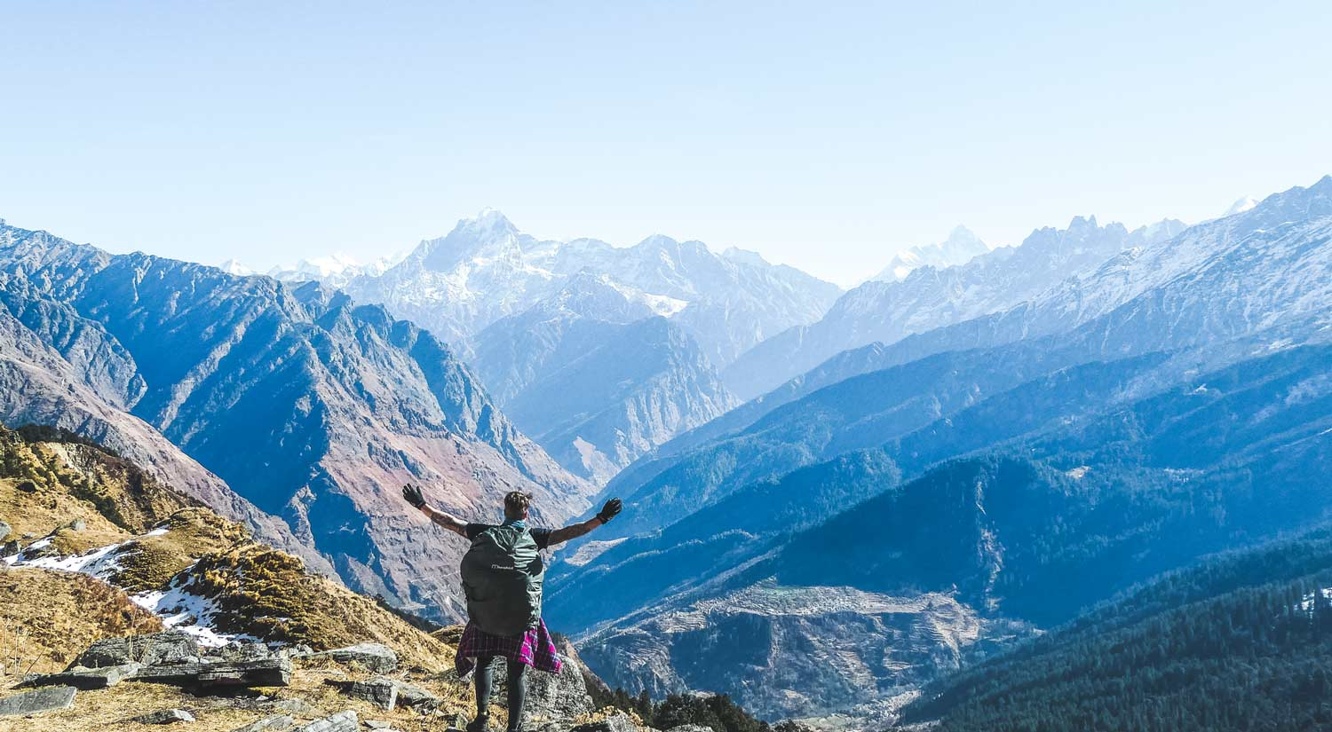 The best Himalayan travel adventure on earth: 3 day Kuari Pass Trek. A man stands with his arms spread on top of a mountain looking out over the Himalayas