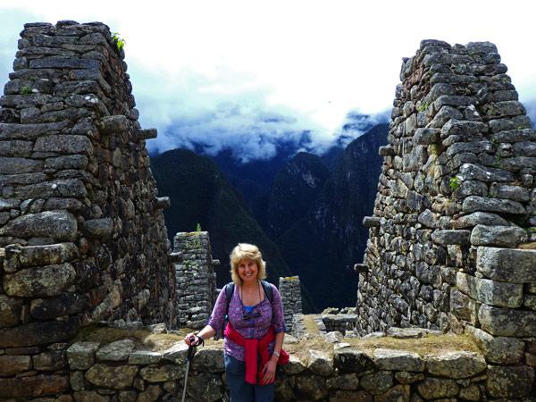 Trekking the Inca Trail to Machu Pichu. A woman standing in front of a building in Machu Pichu