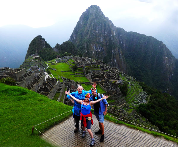 Trekking the Inca Trail to Machu Pichu. Three people standing in front the city of Machu Pichu