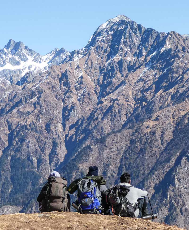 The best Himalayan travel adventure on earth: 3 day Kuari Pass Trek. Three men sit on top of a himalayan mountain looking out to another