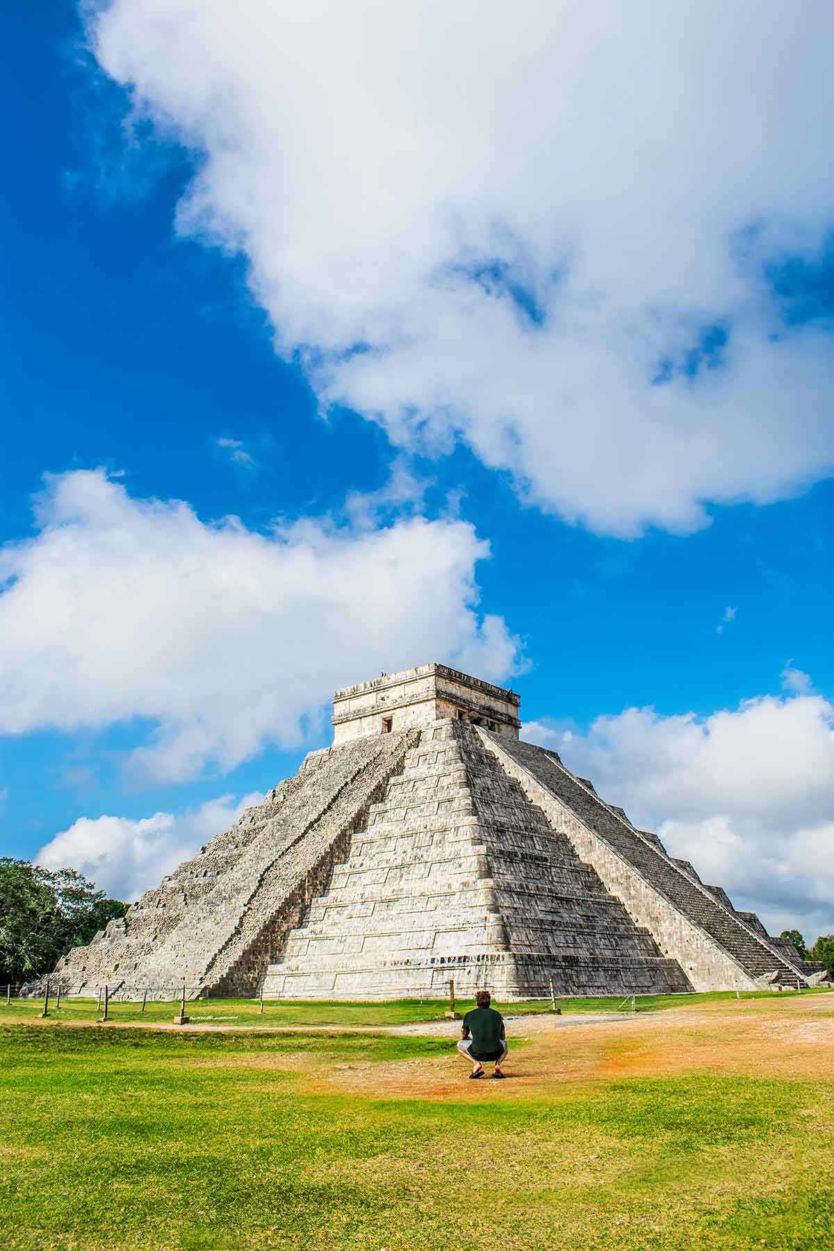 20 EPIC Valladolid Instagram spots for travelling Mexico. A man kneels in front of the main pyramid at Chichen Itza