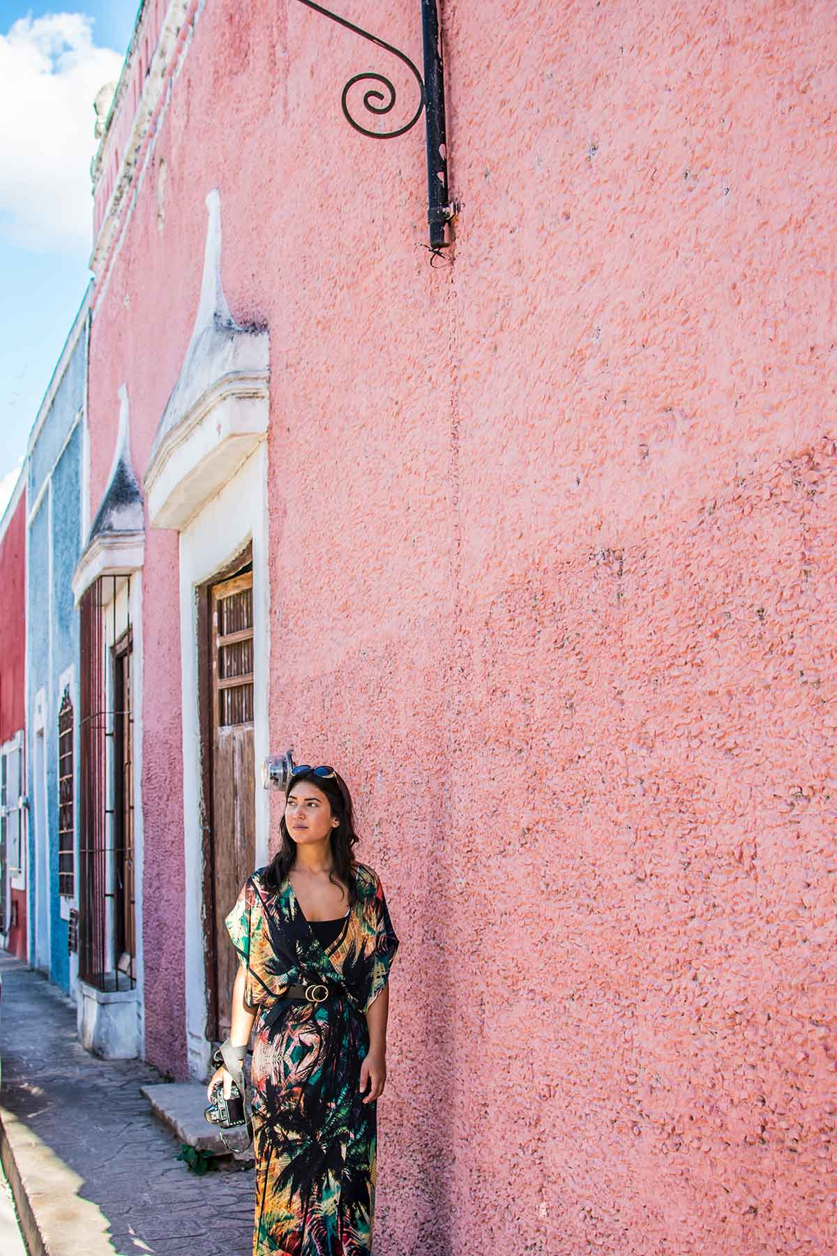 20 EPIC Valladolid Instagram spots for travelling Mexico. Woman walks along side a pink wall of the The multi coloured walls of Calle de los Frailes street