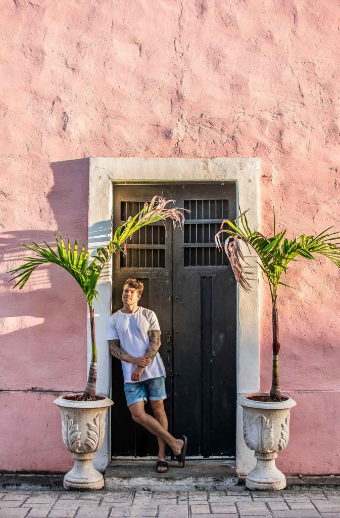 20 EPIC Valladolid Instagram spots for travelling Mexico. A man stands in the door way of a pink building