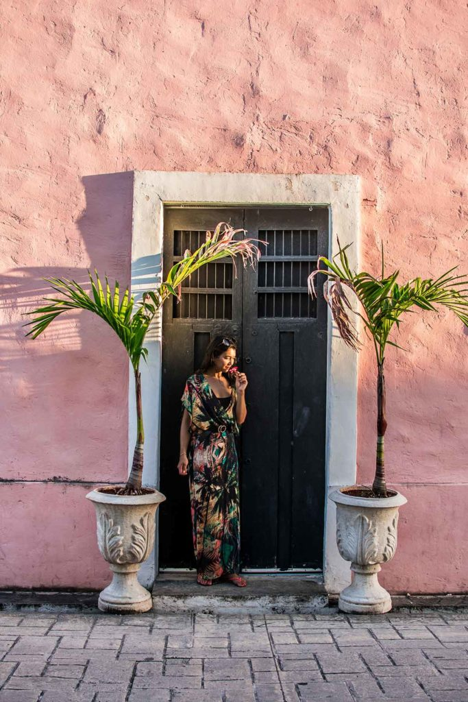 20 EPIC Valladolid Instagram spots for travelling Mexico. A woman stands in the door way of a pink building