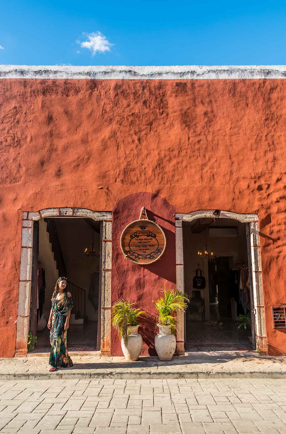 20 EPIC Valladolid Instagram spots for travelling Mexico. A woman walks over the road with a vibrant red Mexican building behind her in Valladolid.