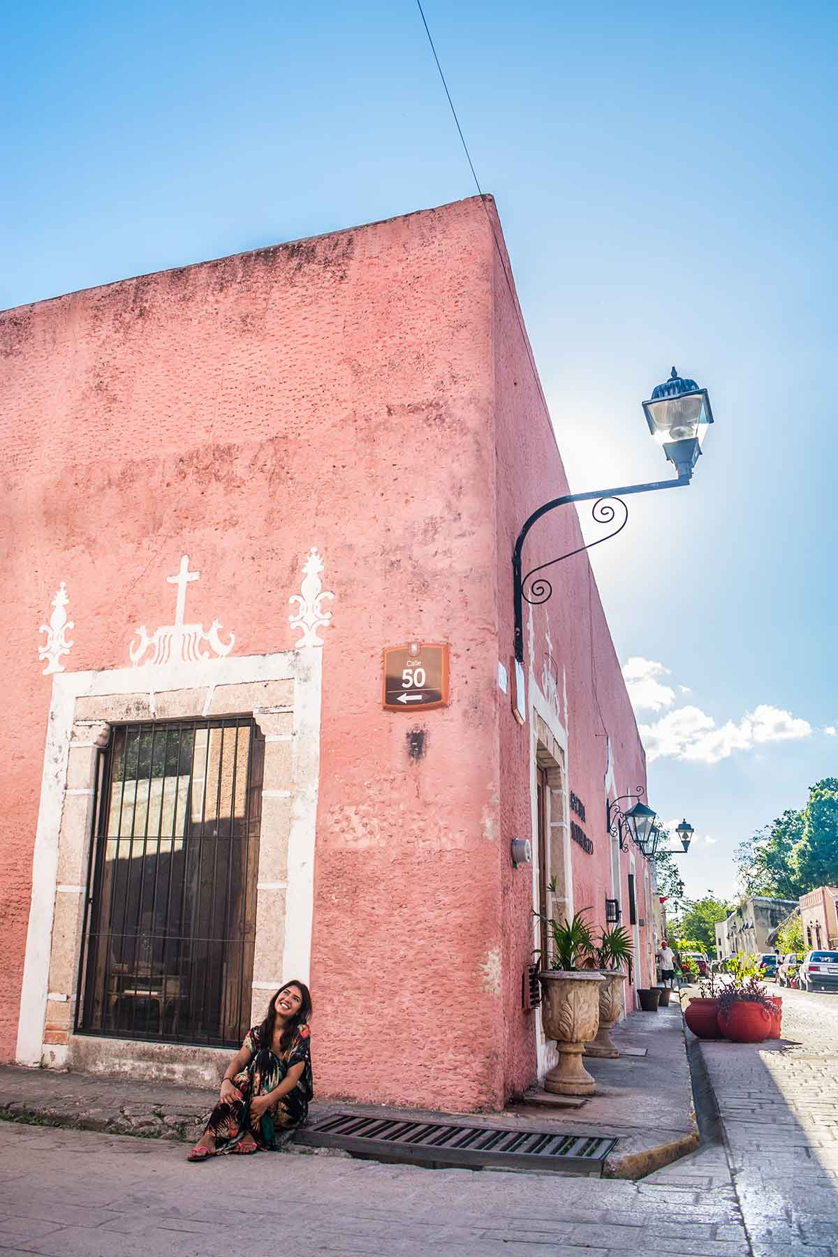 20 EPIC Valladolid Instagram spots for travelling Mexico. A woman sits on a street corner of Calle 50 with a pink building behind her