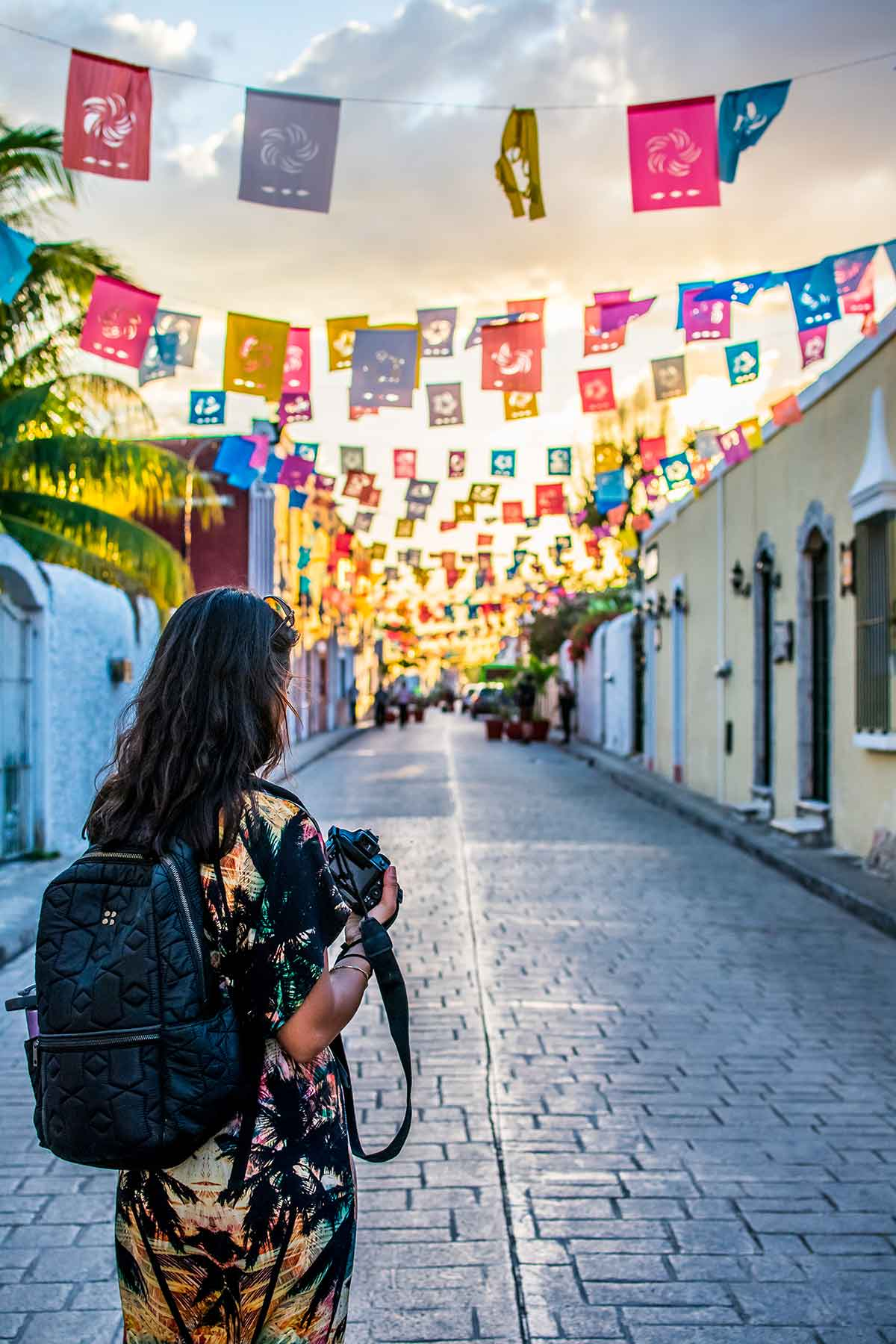 20 EPIC Valladolid Instagram spots for travelling Mexico. A woman stares down Calle de los Frailes street bunting