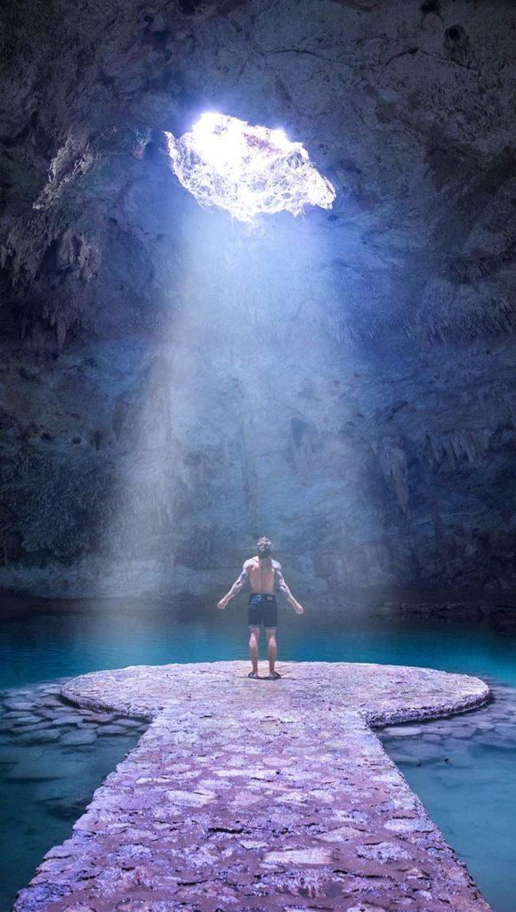 20 EPIC Valladolid Instagram spots for travelling Mexico. A man stand in the middle of Cenote Chan Suytun with the light coming down on him and the water surrounding him