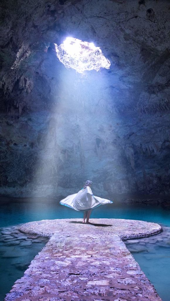 20 EPIC Valladolid Instagram spots for travelling Mexico. A woman stand in the middle of Cenote Chan Suytun with the light coming down on him and the water surrounding him