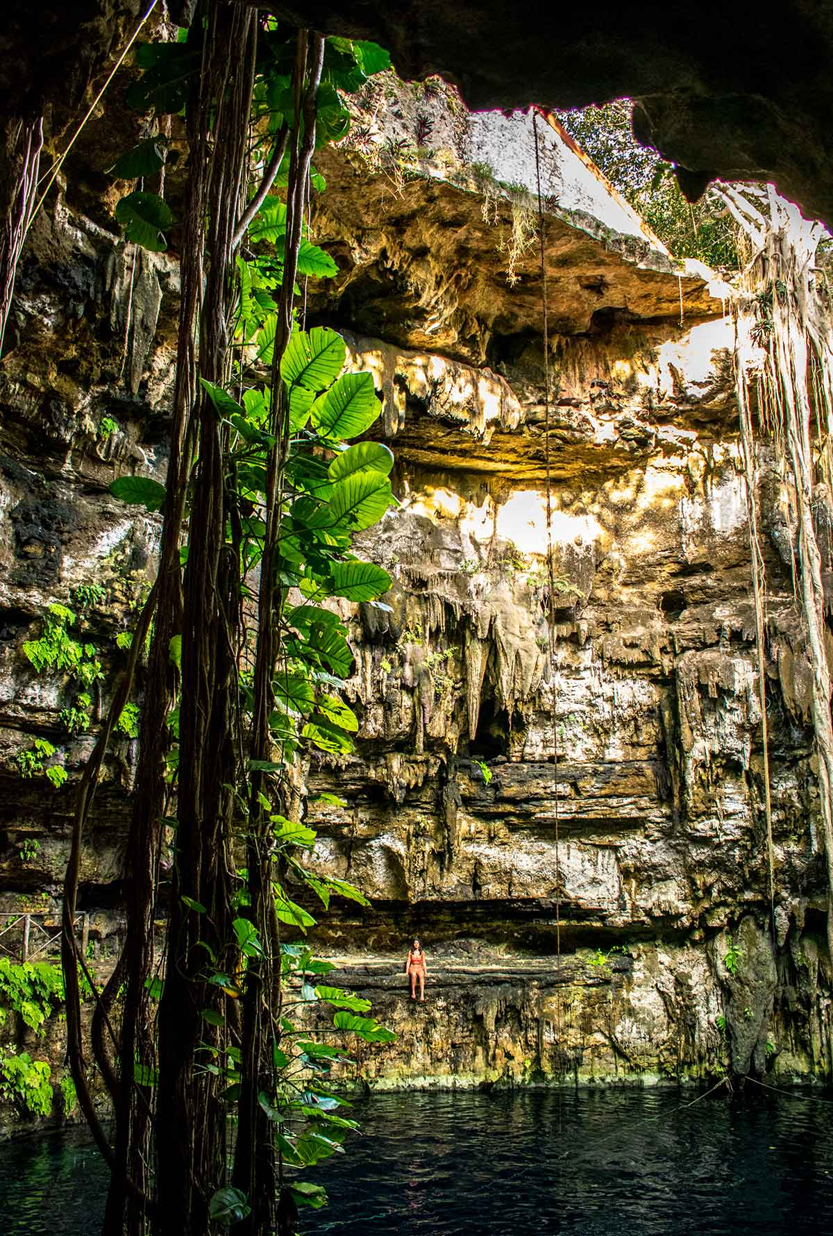 20 EPIC Valladolid Instagram spots for travelling Mexico. A woman sits on her own on the side of Cenote Oxman
