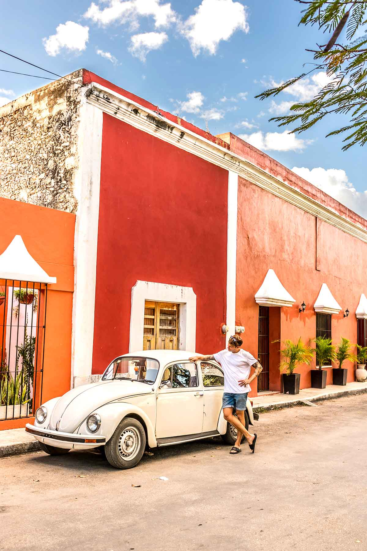 20 EPIC Valladolid Instagram spots for travelling Mexico. A man leans on an old beetle in the streets of Valladolid outside some colourful buildings