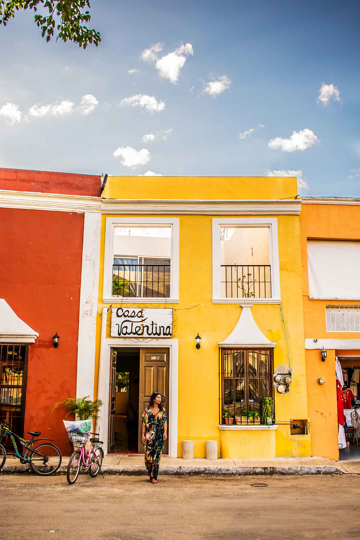 20 EPIC Valladolid Instagram spots for travelling Mexico. A woman walks across a street with a cute yellow store behind her