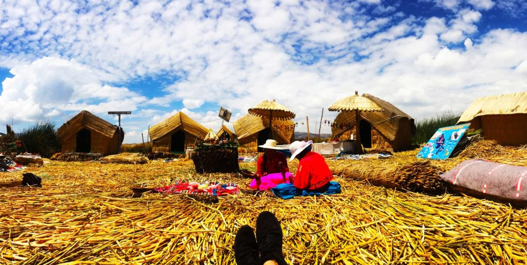 Why travelling Lake Titicaca is stunning but also a tourist trap. A person sits on the floating hay bails of Lake Titicaca
