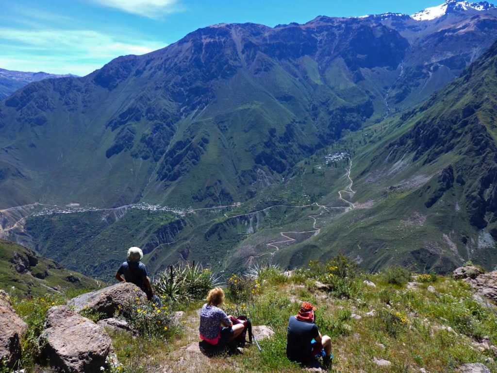 Here's why trekking Colca Canyon took my breath away. Three people sit looking over colca canyon