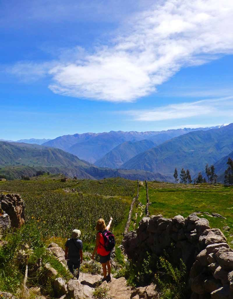 Here's why trekking Colca Canyon took my breath away. A woman points to the distant mountains