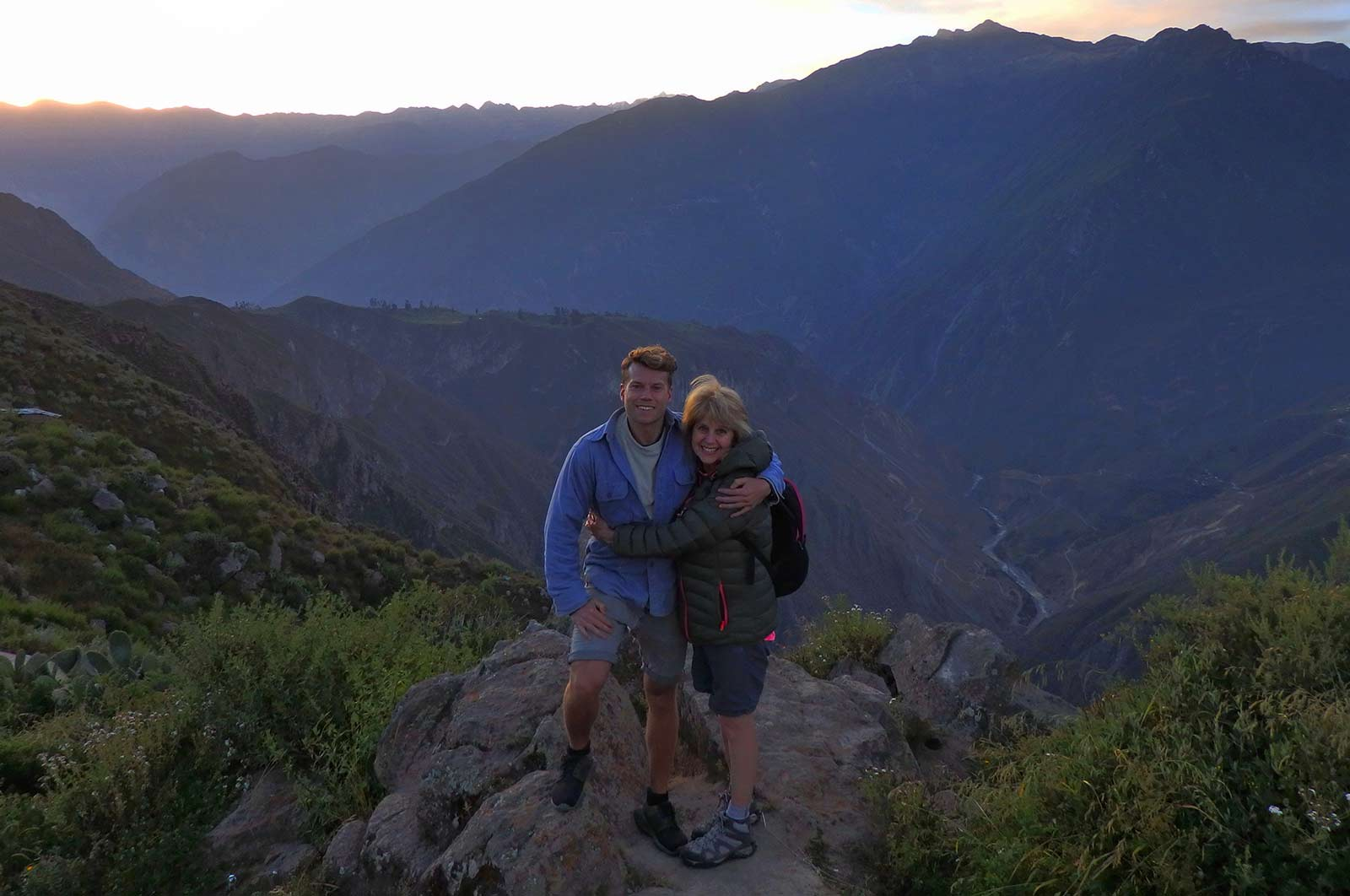 Here's why trekking Colca Canyon took my breath away. A son and mum hug with Colca Canyon in the backdrop
